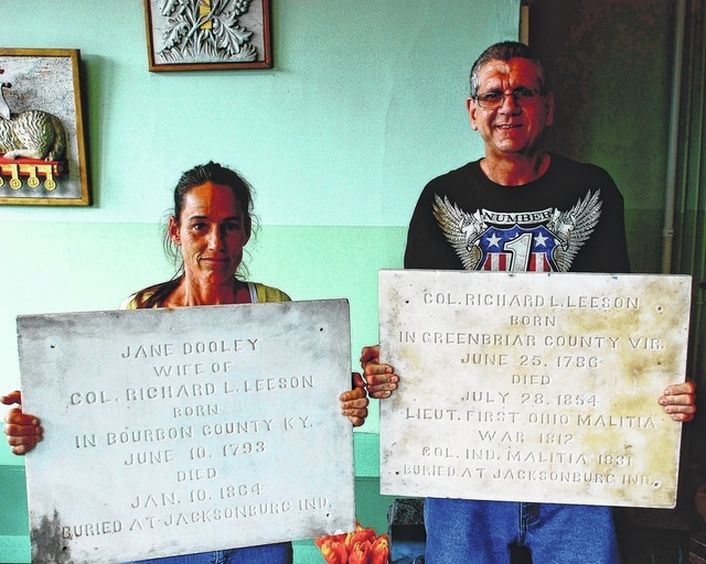 Matt Leeson, right, and his wife, Melanie Leeson, left, hold the two stones/crypt doors made for Mr. Leeson's great-great-great grandparents. The stone held by Mr. Leeson was discovered in 1979 at Boldman Printing in Urbana and claimed by Mr. Leeson in May 2004. The stone held by Mrs. Leeson was discovered in the early 1970s at Urbana Monument Company, 113 E. Church St., and received by the Leesons on Friday during a visit to the business.