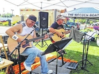 "Rob Neeley, left, and Charlie Knott provide two-part entertainment to the crowds at Russells Point Harbor for the Wooden Keels and Vintage Wheels on July 18. This was the third year that Knott has played for the show and he said that he always enjoys the gig. ""This is a cool place just to come and hang out for a while,"" he said."