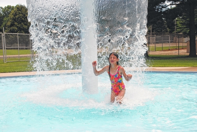 Parker Drewery, age 7, plays in the water umbrella fountain at Melvin Miller Park pool on Thursday. Temperatures were closer to 80 degrees with bright sunshine and no rain on the radar after nearly three weeks of persistent and drenching rains. Showers are possible in the area tonight through Sunday.