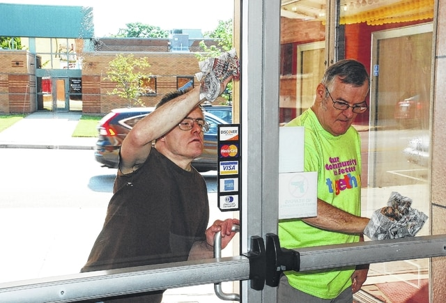 Individuals from the Person Centered Services Lawnview Career and Life Enrichment Center are helping revitalize the Gloria Theatre in Urbana by volunteering services every Wednesday. Pictured cleaning the front doors are Joe Glismann, left, and Ed Bailey, right.