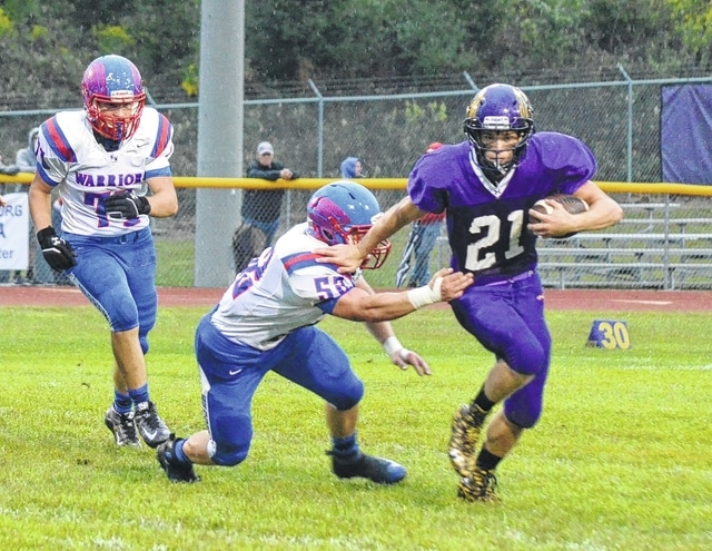 Mechanicsburg's Phil Cook breaks through an arm tackle against Northwestern Friday night.