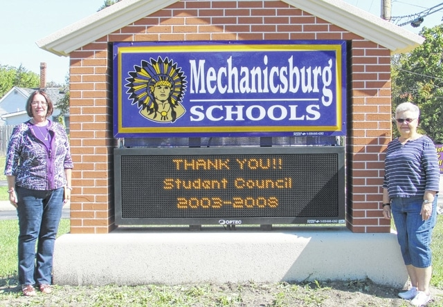 Mechanicsburg High School English teacher Kim Poland, left, and retired business teacher Judi Trainer stand by the new digital sign at the school district. The two former co-advisors of Student Council helped council members from 2003 to 2008 raise money to build the sign.