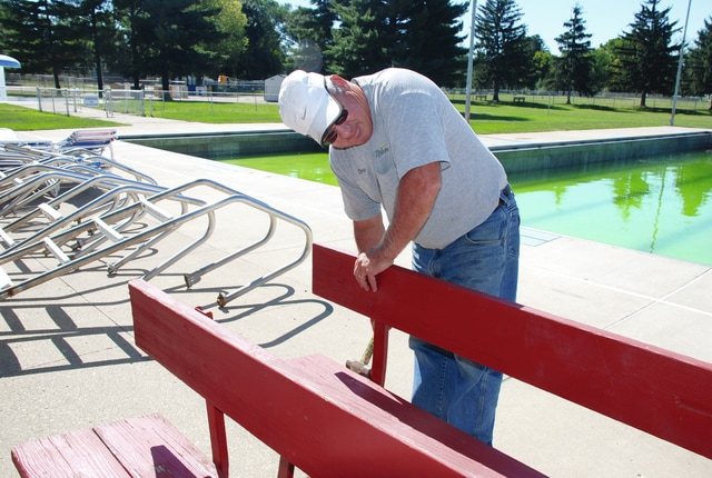 Urbana Parks and Recreation Superintendent Chris Stokes works on putting away the city pool fixtures for the cold season. It was a mild, sunny day for taking care of outdoor chores on Monday. The weather is expected to be sunny, mild and dry all week.