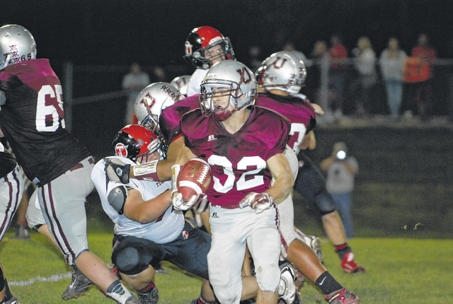 Urbana's Ezra Lee turns the corner deep in Tecumseh territory during the first half of Friday night's game.
