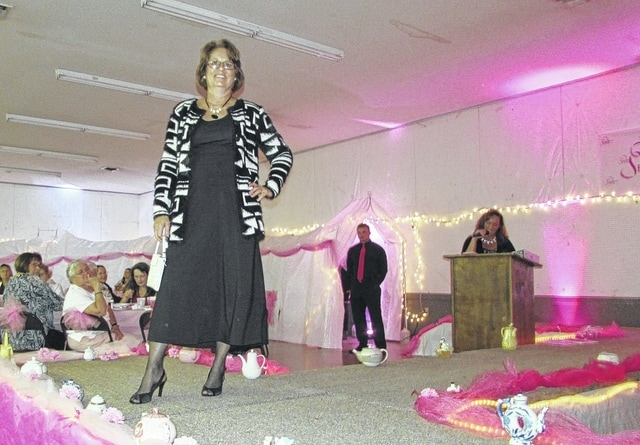 Breast cancer survivor Nona Cooper models an outfit from Guild Gallery in Urbana at Fashions to a Tea on Thursday.