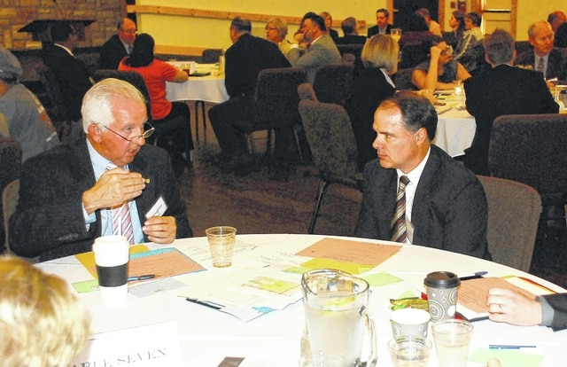 CRSI CEO Than Johnson, left, and Champaign County Health Commissioner Jeff Webb, right, discuss what can be done to address local health care concerns during a summit held Wednesday at the Urbana Christian Conference Center, 1778 W. state Route 29.