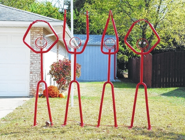 The Stokes residence at 547 Dorothy Moore Ave. in Urbana features two distinct pieces of artwork dedicated to The Ohio State University - a figure holding a mailbox decorated to resemble an OSU football helmet and four figures spelling out O-H-I-O. The Buckeyes host Penn State today at 8 p.m.