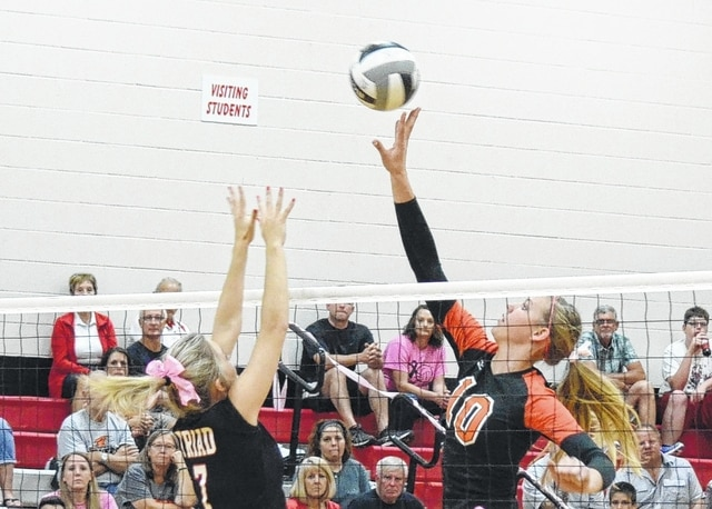 West Liberty-Salem's Jamie Peterson (right) taps a ball over the outstretched hands of Triad's Allyssa Eaton on Monday.