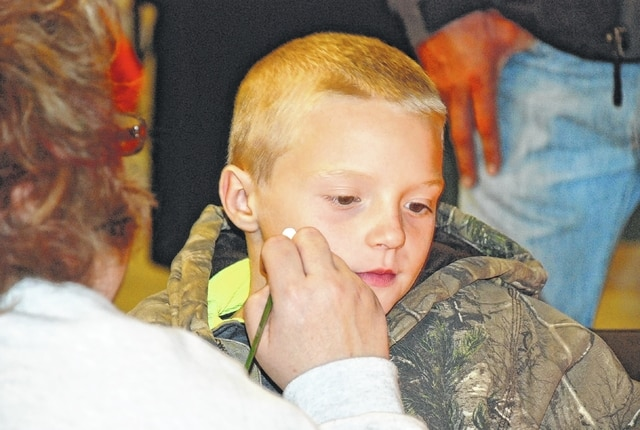 Sally Engle paints a skull on the face of seven-year-old Nicholas Kensler during the Boo in the Bog Saturday night at Cedar Bog.
