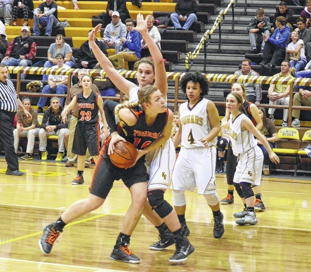 West Liberty-Salem's Jamie Peterson tries to plow her way to the basket against the defense Monday at Kenton Ridge High School.