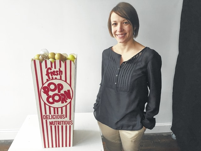 """Lydia Hess is the Administrative Manager of the GrandWorks Foundation/Gloria Theatre. She is a member of the Arts Council's Board of Trustees. She has created a replica popcorn box comprised of old incandescent hand-painted light bulbs from the theatre's marquee. She would like to thank her father, Steve Hess, for creating her wooden popcorn box """"canvas."""" Lydia is one of 15 """"good people"""" producing """"bad art"""" for the 2016 Champaign County Arts Council's annual fundraiser."""