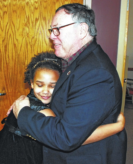 Crissy Moye, 9, of Urbana, hugs Urbana Mayor Bill Bean during an after-school visit to the municipal building on Wednesday. The girl recently wrote to Bean, who agreed to meet with her to answer questions regarding the duties of a mayor.