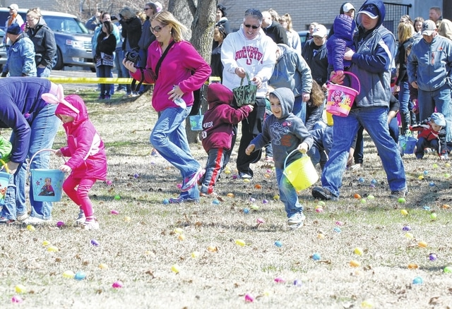 Children and adults search for Easter eggs during the 2015 community Easter egg hunt. This year's event will take place at 12:30 p.m. Saturday at the hill in front of Urbana High School.