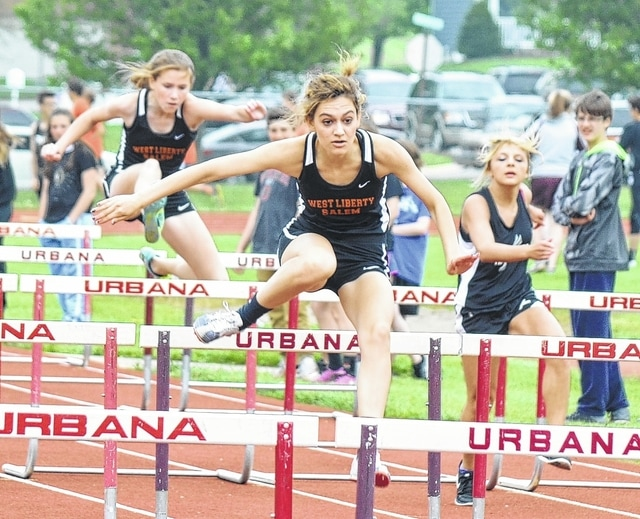 West Liberty-Salem's Caylee Karg leaps over a hurdle during the 100-meter competition at Urbana on Tuesday. Karg won the competition, helping to power the Tigers.