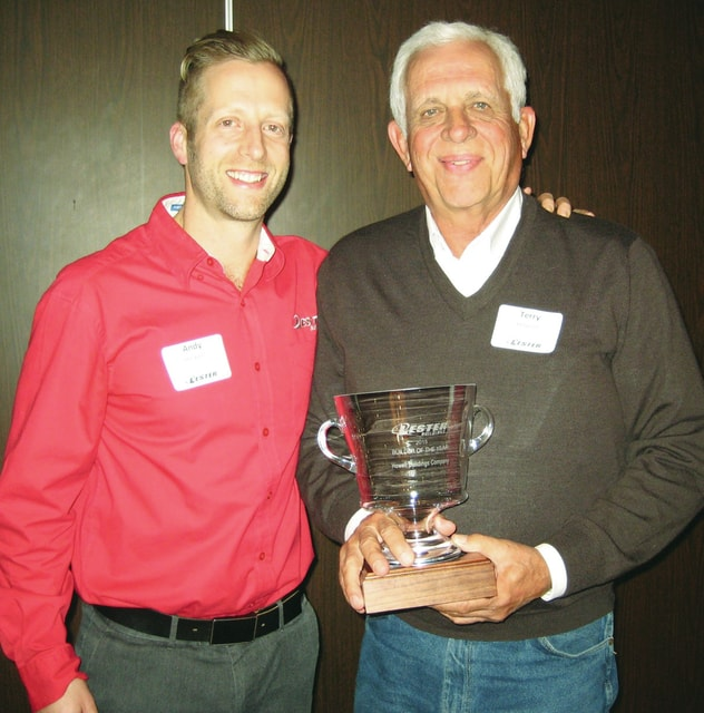 Terry Howell's son, Andy, district sales manager for Lester Building Systems, presents him Lester Building Systems' Dealer of the Year Award at the company's Charleston, IL, facility.