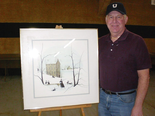 "Local auctioneer Steve Mabry is pictured displaying a P. Buckley Moss signed artwork which will be auctioned during the Champaign County Preservation Alliance's annual Décor and More auction to be held Saturday, April 30, beginning at 1:01 p.m. Donations are being accepted April 25-28 from 11 a.m. to 3 p.m. at Mabry's Auction Gallery, 1301 N. Main St. Marty Hess and Vince Gonzalez, emcees for the auction, guarantee an afternoon of fun and a great variety of ""treasures"" to sell. Contact Barbara Perry with any questions, 653-4776. Proceeds from the auction will fund the Commercial and Retail Façade Grant program sponsored by the CCPA."