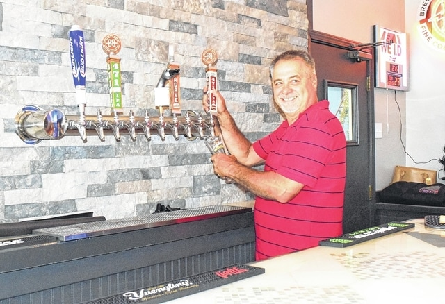 Vintage Drive Thru and Cafe and Wing Bar co-owner Mike Fraley prepares to pour a beer at the newly renovated restaurant, set to open Monday.