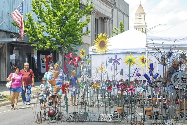 Patrons of the annual Art Affair on the Square circle around one of the more popular attractions on Saturday. Colorful metal art for gardens was on display just north of the square. Concessions and other activities were also part of the day-long event that drew shoppers downtown to Monument Square District.