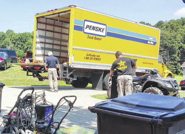 Deputies load up items into a large moving truck Tuesday morning at the Johnson residence in Jackson, Ohio. An investigation alleges Johnson purchased mowers, vehicles, a camper, trailers, tools, televisions, guns, furniture and appliances with village money.