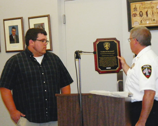 Urbana resident Larry Lawson III, left, is presented with the Urbana Police Division's Civilian Service Award by Urbana Police Chief Matt Lingrell. Lawson was recognized for his actions that helped arrest a registered sex offender.
