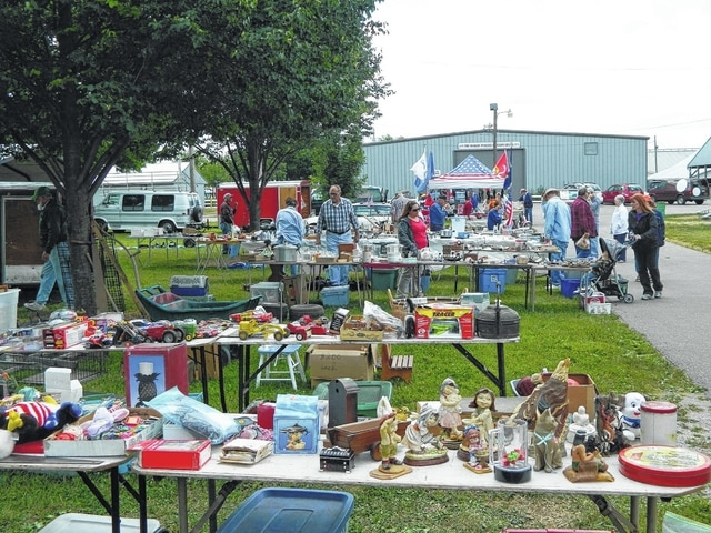 Individuals attending a past Urbana Antique Show & Flea Market at the Champaign County Fairgrounds make their way through a line of outdoor vendors.