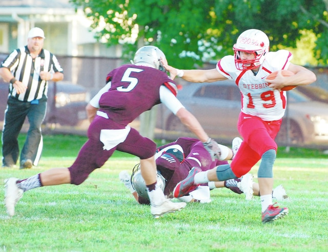 Stebbins quarterback David Hickey breaks a tackle by Urbana's Max Niswonger (5) during Friday night's game at UHS.