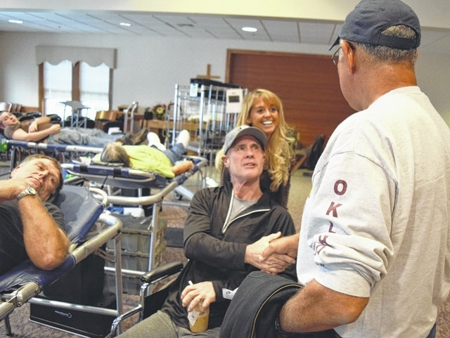 Scott and Cindee Boyd greet friend and donor John Dennis. Ed Fout, Mrs. Boyd's step-father, left, donates blood.
