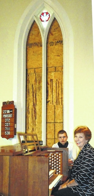 Organist Sharon McCall and son Chris, an acolyte, adjust to the windowless interior.
