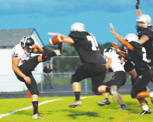 Graham's Michael Shook blocks a punt by Greenon's Juan Cervantes during the first quarter of Friday night's game at Graham.
