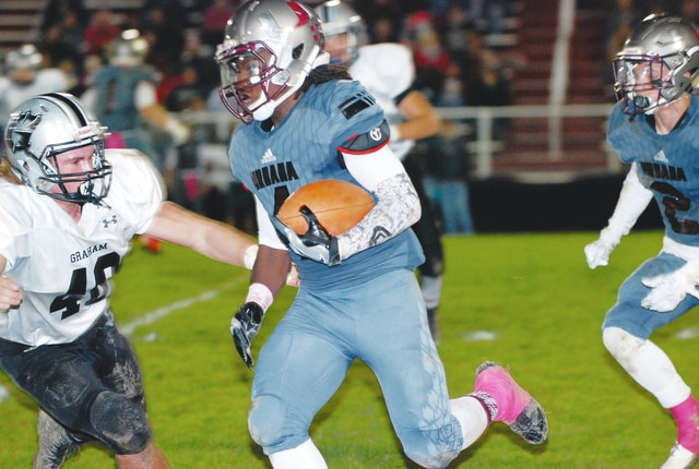 Urbana's Herbie Jackson fights for yards against Graham's Lane Thompson during Friday night's game at UHS.