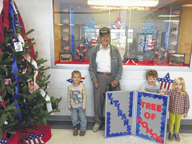 Y member and veteran Warren Vanscoy stands next to the Honor Tree with Y preschoolers Genevieve Lamb, Braedy Fox and Brady Funderburgh. He served in the U.S. Air Force 1942-45 and fought in WW2. He was a 3-stripe sergeant for the Air Force's 66 AAF Base Unit and Weather Observer 784. He received the American Theater Ribbon, Good Conduct Medal, European-African-Middle East Theater Ribbon and World War 2 Victory Medal.