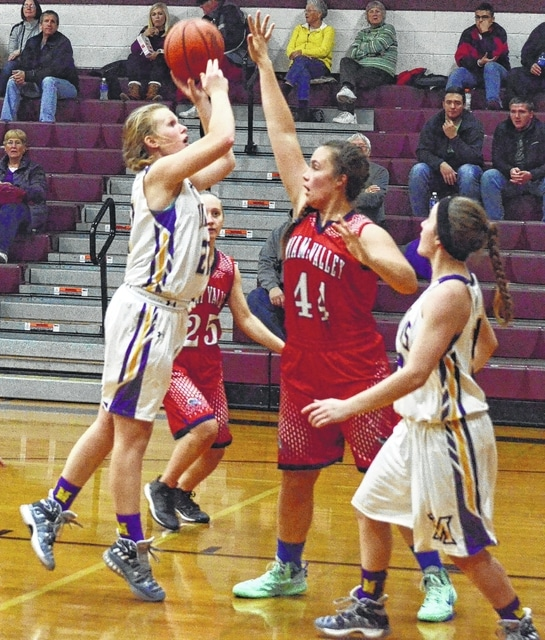 Mechanicsburg's Morgan Hamby (left) shoots over Miami Valley's Molly Lyon on Friday at the Skeeter Classic at Urbana High School. Hamby had 18 points and 12 rebounds.