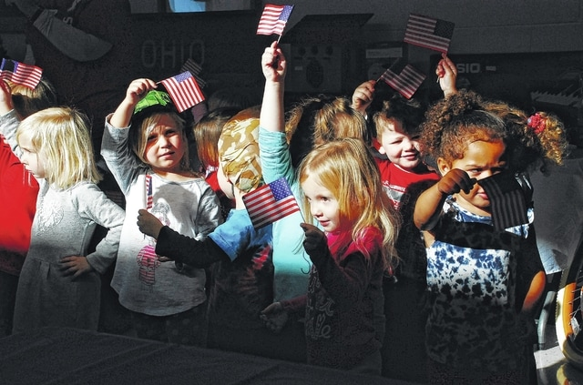Preschoolers wave American flags while singing a patriotic song during the YMCA's Veterans Appreciation Pancake Breakfast on Thursday in Urbana. Today is Veterans Day as observed across the United States. Events are planned around the area today and this weekend. Log on to www.urbanacitizen.com for a complete listing.