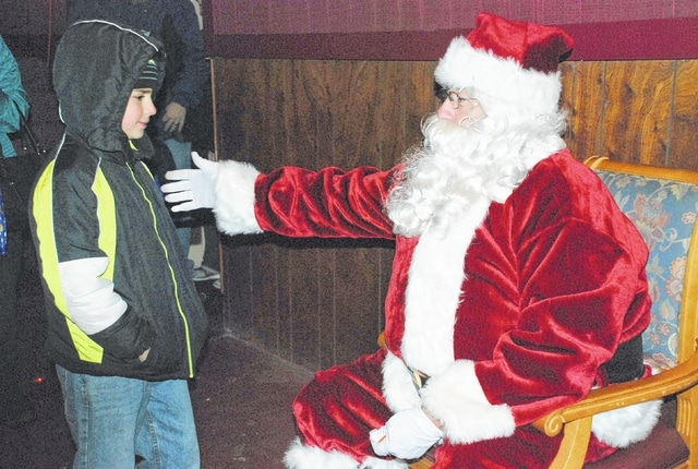 Santa greets Joran Mouton on Friday at the Gloria Theatre. Santa arrived in Urbana as part of a parade of horses through the downtown. Santa will return Friday from 5-8 p.m. and Saturday, Dec. 3 from 11 a.m. to 2 p.m. to visit with local children.
