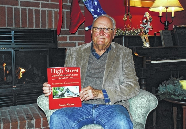 """Daniel Walter holds a copy of his first published book, """"High Street United Methodist Church: A Comprehensive, Illustrated History,"""" inside his Urbana home."""