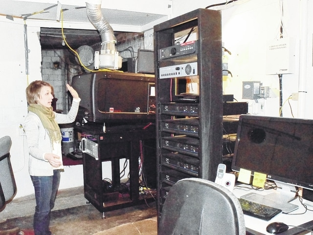 GrandWorks Foundation Administrator Lydia Hess shows off the new equipment at the Gloria Theatre. The sound system was donated by Regal Cinemas, through the assistance of retired Vice President of Technical Services Roger Frazee. Frazee's father, Jack, was the manager at the Gloria from 1950-66.