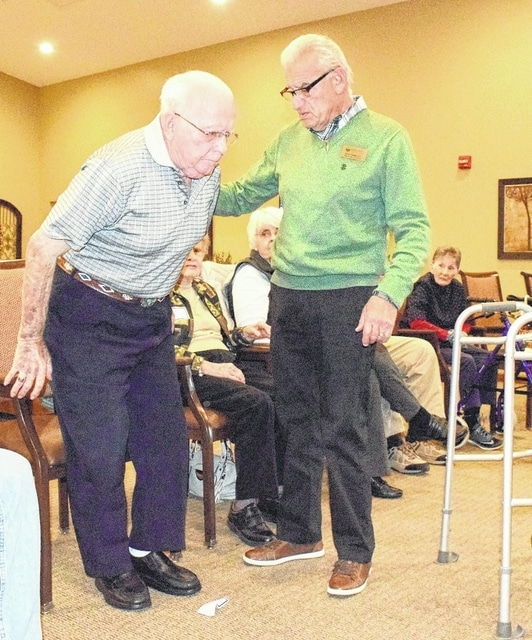 Dale Baker, left, demonstrates the techniques he learned to make getting in and out of a chair easier, with physical therapist Robert Kahn helping out. Baker is part of a group that helps Parkinson's disease patients maintain their mobility.