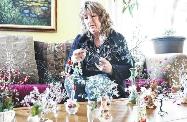 Leanna Brulport, of Sidney, makes stone-covered trees by twisting wires together with pliers. The craft has helped her recover from a stroke.