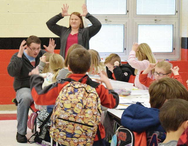 Triad Elementary American Sign Language Interpreter Makenzie Miller, standing, teaches elementary students holiday-themed signs at her American Sign Language Club session Wednesday. Miller started the club to help students communicate with first grader Carson Jackson.