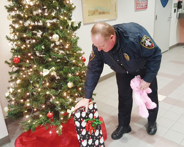 Urbana Police Officer Todd Pratt places Christmas presents under The Giving Christmas Tree. As part of an annual event, the Fraternal Order of Police, Lodge 93, sought out children in need of an extra Christmas present this season. Sgt. Josh Jacobs said members of Lodge 93 and the Urbana Police Division will begin delivering presents to just under 100 children today.