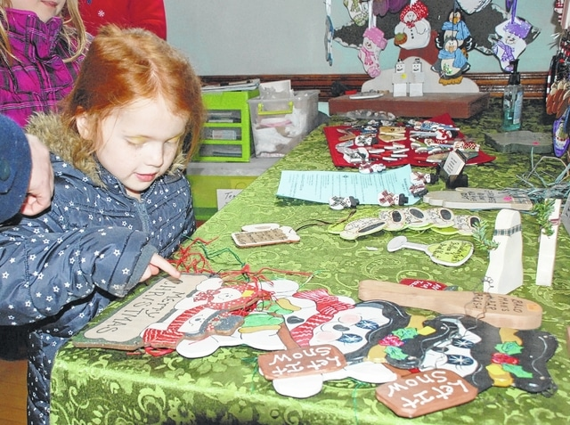 Five-year-old Allie Wage admires Christmas gift items displayed on a table during the craft sale in Mechanicsburg Masonic Lodge on Saturday. The craft show was part of Christmas in the Village, which included a parade, Santa's arrival, decorated cookies for sale and several musical shows at the historic Second Baptist Church.