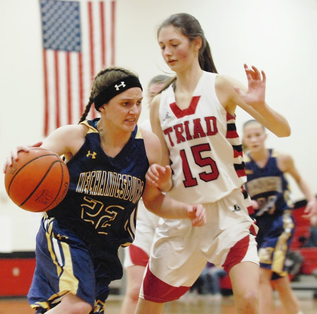 Mechanicsburg's Mikayla Dodane (left) dribbles past Triad's Makenzie Cauley en route to a layup during Thursday night's game at Triad.