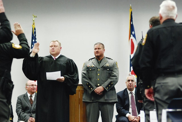Champaign County Judge Brett Gilbert (left) swears in the deputies of the Champaign County Sheriff's Office as Sheriff Matt Melvin (standing at right) looks on during Wednesday's ceremony at the Champaign County Community Center. County officeholders who were voted in during the November 2016 general election were sworn in during the ceremony. All incumbents on the ballot were re-elected and all are Republicans. Seated at left is Champaign County Coroner Dr. Joshua Richards and seated on the right is Champaign County Prosecutor Kevin Talebi.