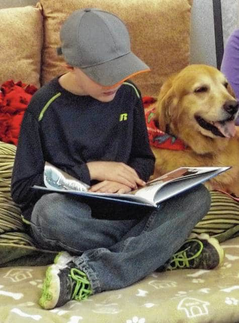 Christian Brewer reads to Izzy during a past PAWS for Reading program at the Mechanicsburg Public Library.
