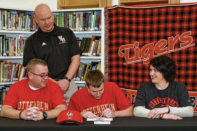 """West Liberty-Salem senior baseball player Tyler Louden signs his official letter of intent to play baseball at Otterbein University. He will major in Criminal Justice. Pictured are Louden with his parents, Rob and Allyson, and Tigers head coach Jon Payer. """"Tyler is a great kid, fierce competitor, great work ethic, and a pleasure to have on the team. He is a true leader on the field and in the classroom,"""" said Payer."""