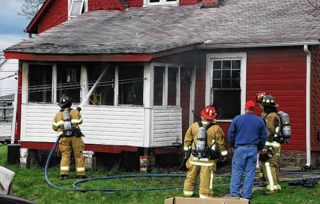 Crews from five area fire departments responded to a house fire at 109 W. Sandusky St. in Mechanicsburg on Monday. Several firefighters, pictured, look on from the rear of the structure as another firefighter sprays the home with water.