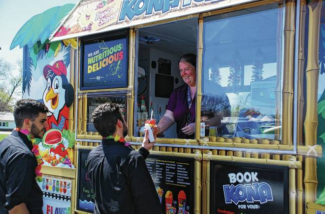 """Sarah Lay, owner of Kona Ice of Troy, serves up free shaved ice to Justin Lord, right, and Anthony Baglione, left, on Tuesday at the Champaign County Library. Lord and Baglione, who work for L.A. Catering out of Columbus, were in Urbana for a Meals on Wheels event at the library and couldn't pass up a free treat. Lay said she was handing out free shaved ice to the public as part of Kona Ice's National Chill Out Day, held every year on Tax Day as a way for the company to help Americans """"chill out and relax"""" during one of the most stressful days of the year."""