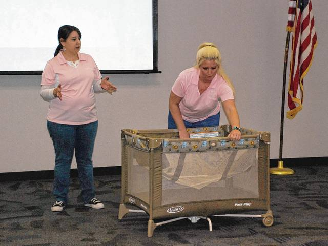 Champaign Health District Director of Nursing Stacey Thomas, left, and Ashley Carr, a health professional with the county's WIC Division, show new and expectant mothers how to set up a Graco Pack 'n Play during a safe sleep class held on April 13 at the Champaign County Community Center.