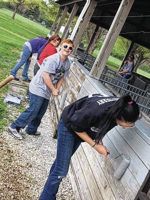 Students from Graham Local Schools fanned out on Friday to assist in community betterment projects in the St. Paris and Urbana areas for a project known as Service Day. The event was a collaboration between Champaign County Board of Developmental Disabilities/Community Connections and the United Way. Pictured, a group of students pitches in painting the swine barn at the Champaign County Fairgrounds.