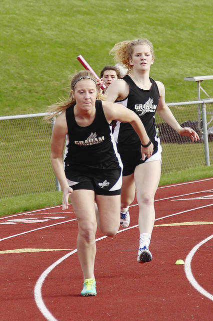 Graham's Kayla Tullis and Carly Carafa compete in a relay event at a track meet held at Urbana earlier this week.